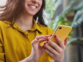 Image recadrée d'une jeune fille heureuse utilisant un smartphone tout en se relaxant à la maison.
