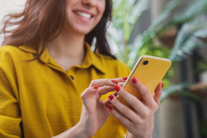 Imagen recortada de una chica feliz utilizando un dispositivo smartphone mientras se relaja en casa