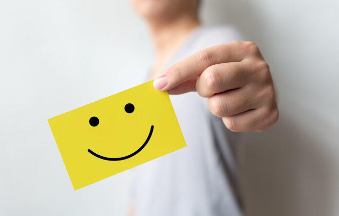 Encuesta sobre la experiencia del servicio al cliente y la satisfacción del negocio. Hombre sosteniendo una tarjeta amarilla con una cara sonriente