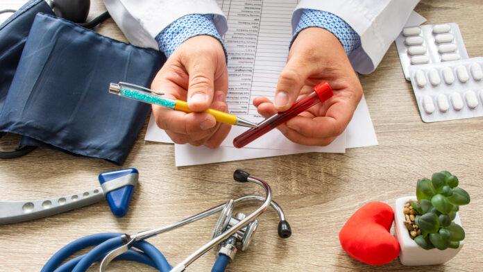 Médecin pendant une consultation tenant dans sa main et montrant au patient un tube de laboratoire avec du sang. Consultation de transfusion, maladies et pathologies du sang et de l'hématologie comme les anémies, le cancer cellulaire, l'hémophilie.