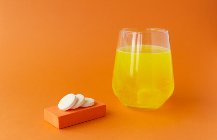 Effervescent vitamins, water-soluble tablets on orange backgrounds