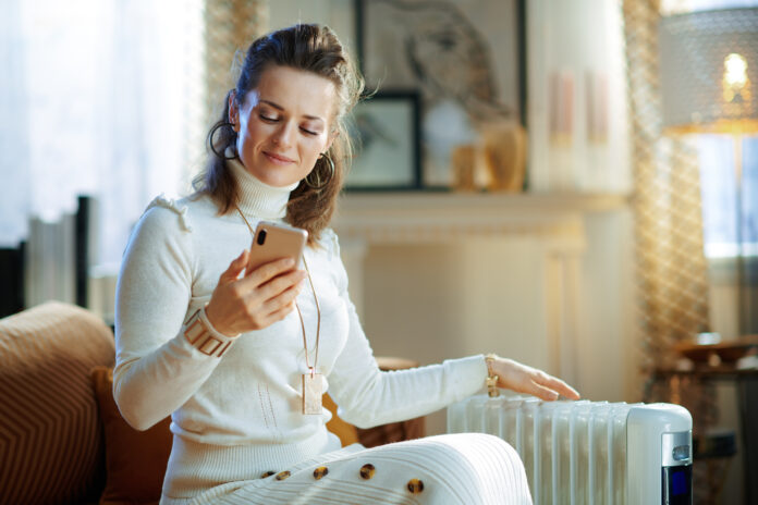 elegant woman in white sweater and skirt at modern home in sunny winter day sitting on couch near white electric oil radiator using smartphone app for temperature control.