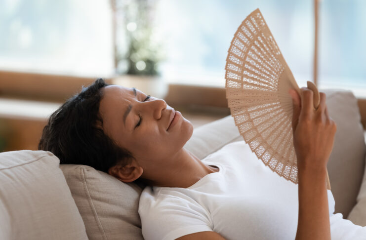 Exhausted biracial young woman relax on sofa in living room breathe fresh air from waver, tired sick African American millennial female rest on couch at home wave with hand fan suffer from heatstroke
