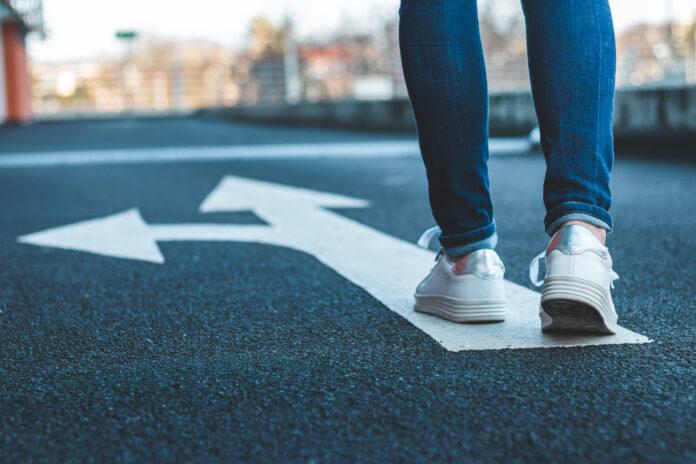 Des jambes de femme portant un jean et des baskets blanches.