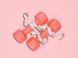 Plan d'haltères sur fond rose. Concept de sport.