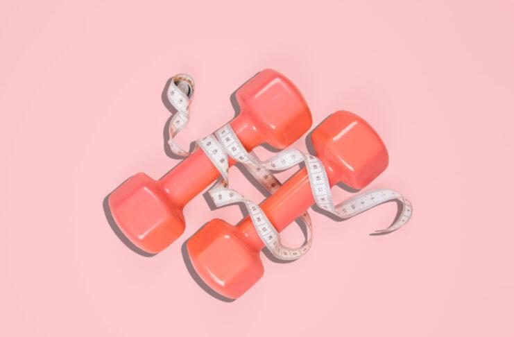 Toma plana de mancuernas sobre fondo rosa. Concepto deportivo.