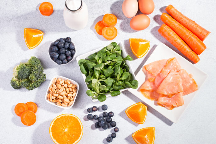 Foods that help maintain eyes healthy, products for keeping good vision. Black board with copy space, assortment of food for eye health on concrete background, flat lay, top view, nobody