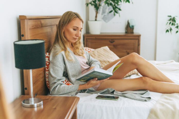 Friendly charming blonde woman reading book on the bed in bright interior