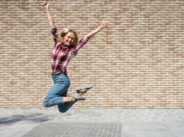 Full length view of happy young university student girl showing thumbs up and jumping against brick copy space wall on background. Successful exam and graduation, education concept