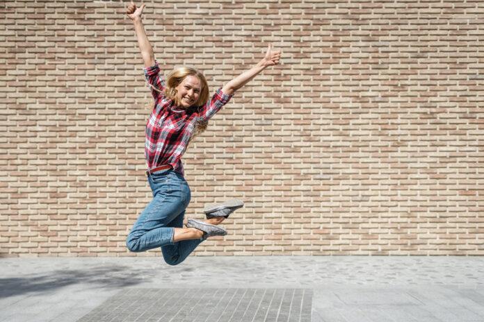 Pełna długość widok szczęśliwy młody student uniwersytetu dziewczyna pokazując kciuki w górę i skoki przeciwko cegły kopiowania przestrzeni ściany na tle. Pomyślnie zdany egzamin i ukończenie studiów, koncepcja edukacji