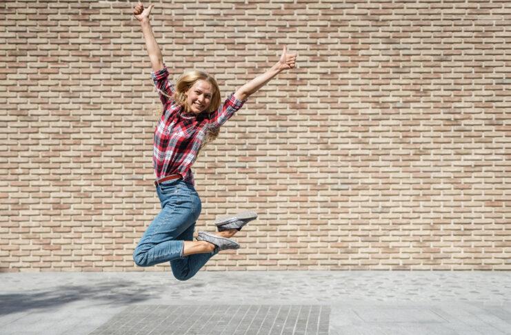 Volledige lengtemening van gelukkig jong universiteitsstudentmeisje dat duimen toont omhoog en tegen baksteenkopie ruimte muur op achtergrond springt. Geslaagd examen en graduatie, onderwijsconcept