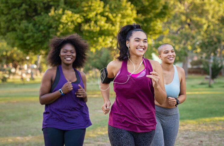 Skupina dívek s křivkami, které společně běhají v parku. Krásné usměvavé mladé ženy běhající v parku za slunečného dne. Běžkyně poslouchající hudbu při běhu.