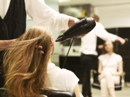 Coiffeuse séchant les cheveux d'une femme avec un sèche-cheveux dans un salon de beauté. Focalisation sélective, espace vide