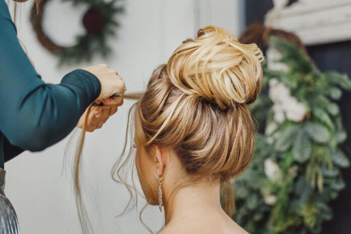 Friseur macht komplexe und schöne Frisur oberen Dutt. Geeignet für Abend und Hochzeit Stil