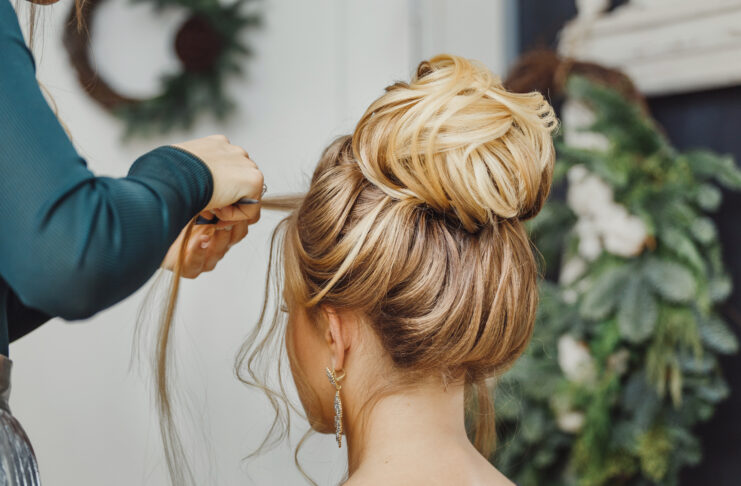 Le coiffeur réalise une coiffure complexe et magnifique avec un chignon supérieur. Convient pour le style soirée et mariage