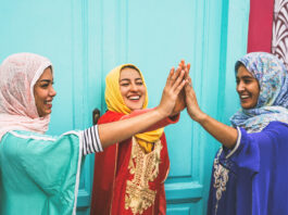 Happy Arabian women stacking hands together outdoor - Young Muslim women having fun and in the university - Concept of empowering, people, religion and team work
