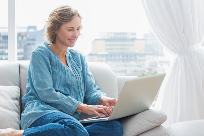 Happy blonde woman sitting on her couch using laptop at home in the sitting room