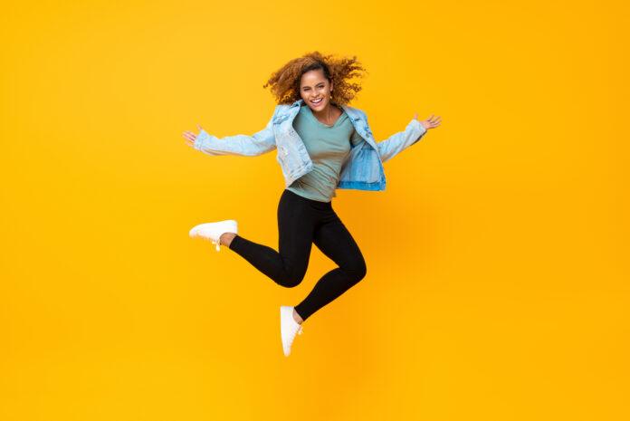 Het gelukkige energieke glimlachen jonge Afro-Amerikaanse vrouw springen die op gele achtergrond wordt geïsoleerd