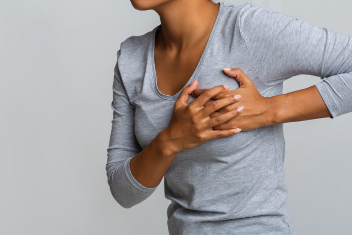 Health problem. Young african woman feeling menstrual cyclic breast pain, touching her chest, close up