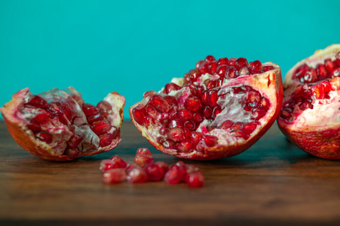 Make tables and backgrounds and take pictures of red pomegranates.