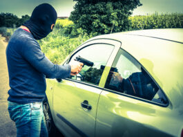 Male thief or terrorist is pointing a pistol on the driver, he trying to steal a car
