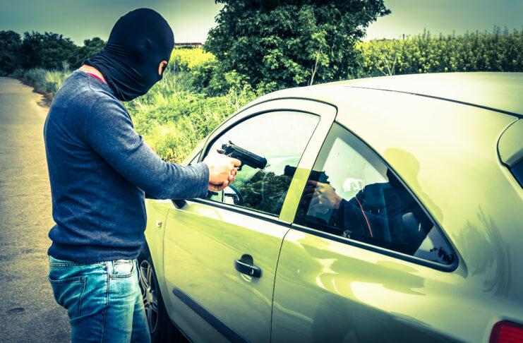 Un voleur ou un terroriste pointe un pistolet sur le conducteur, il essaie de voler une voiture.