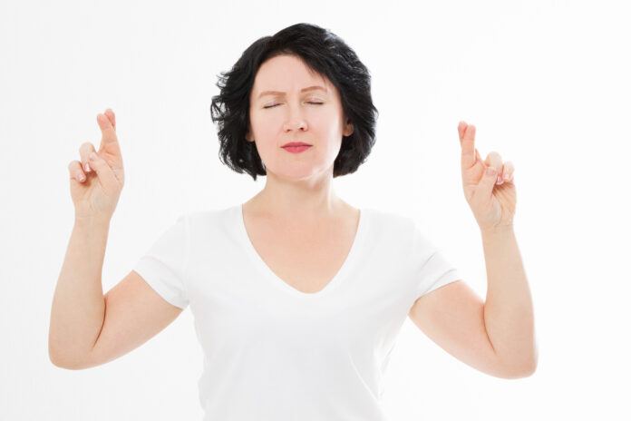 Middle age woman cross fingers for wishing good luck isolated on white background. Template summer t shirt. Copy space
