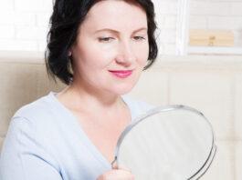 Mujer de mediana edad mirando en el espejo sobre las arrugas de la cara en el fondo de casa. Concepto de cuidado de la piel y antienvejecimiento. Enfoque selectivo