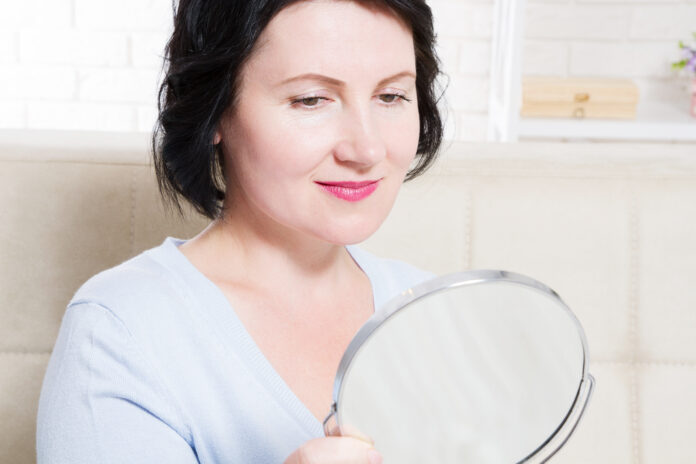 Middle age woman looking in mirror on face wrinkles at home background. Skin care and anti aging concept. Selective focus