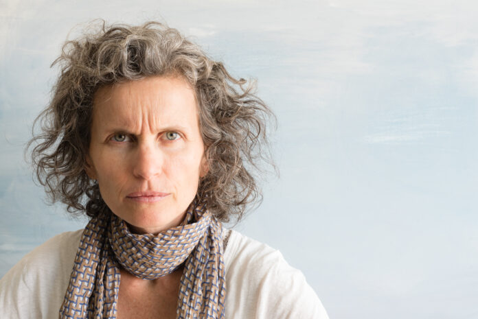 Middle aged woman with grey hair ffowning and looking angry against blue background with copy space (selective focus)