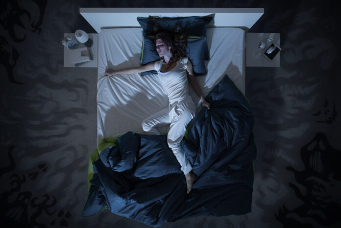 Nervous woman suffering from insomnia and lying in bed late at night, she is awake and restless, top view