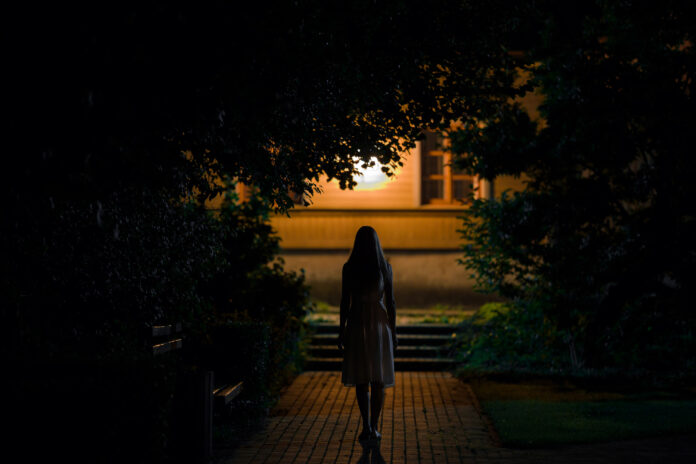 One young alone woman in dress walking on sidewalk through dark park to home in summer black night. Scary moment and gloomy atmosphere. Back view.