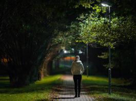 Une jeune femme seule en veste blanche marchant sur le trottoir à travers une allée d'arbres sous la lumière d'une lampe dans une nuit d'automne. Passer du temps seule dans la nature. Ambiance paisible. Vue de dos.