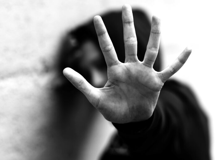 open hand of young girl trying to protect herself from violence with dark dramatic photographic effect