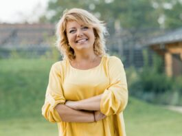 Outdoor portrait of positive confident mature woman. Smiling female blonde in a yellow dress with arms crossed near the house.