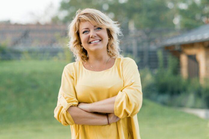 Portrait en extérieur d'une femme mûre positive et confiante. Femme blonde souriante dans une robe jaune avec les bras croisés près de la maison.