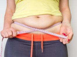 Una mujer con sobrepeso y una cinta adhesiva midiendo la grasa del vientre - concepto de obesidad