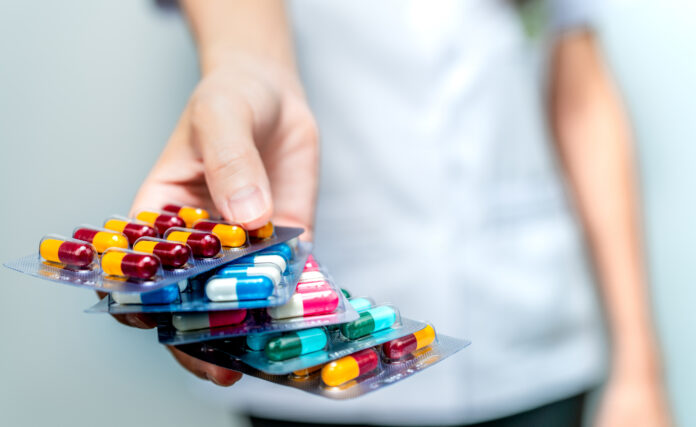 Pharmacist or doctor hand holding pack of antibiotic capsule pills and giving patient or people. Antibiotic drug overuse. Antimicrobial drug resistance. Community pharmacist. Drugstore background.
