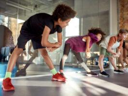 Retrato de un niño sonriendo mientras calienta, haciendo ejercicio junto a otros niños en el gimnasio. Deporte, estilo de vida saludable, concepto de infancia activa. Toma horizontal. Enfoque selectivo