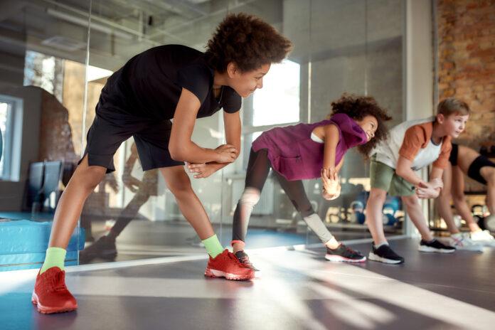 Portrait d'un garçon souriant pendant l'échauffement, faisant de l'exercice avec d'autres enfants dans un gymnase. Sport, mode de vie sain, concept d'enfance active. Plan horizontal. Mise au point sélective