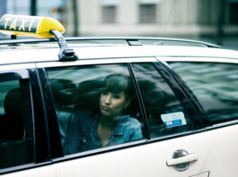 Portrait of a sad young woman sitting in a taxi cab. Berlin, Germany.