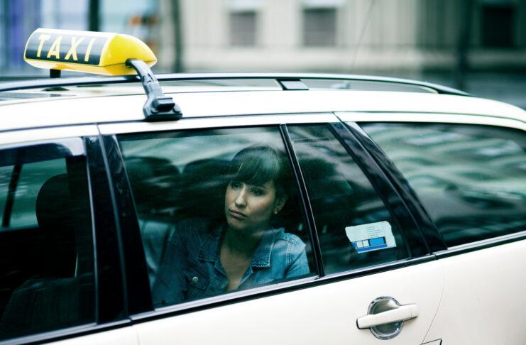 Portrait d'une jeune femme triste assise dans un taxi. Berlin, Allemagne.