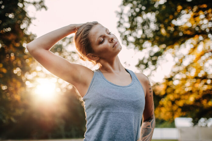 Portrait of healthy young woman stretching her neck outdoors. Caucasian fitness model warming up in park.