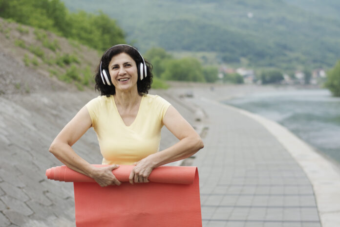 Portrait of mature woman with yoga mat and headphones