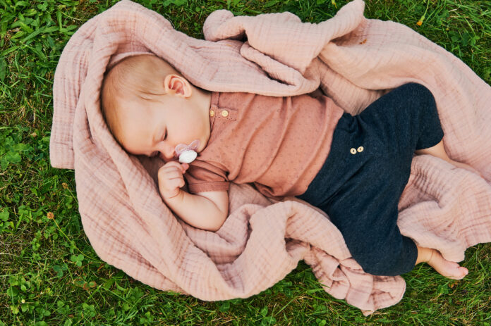 Portrait of sweet baby playing outside, child enjoying fresh air on blanket in garden or park