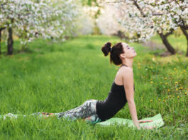 Profile of calm young woman working out on the green lawn in blooming garden, doing stretching exercises, urdhva mukha shvanasana, full length. Unity with nature and inner harmony concept.