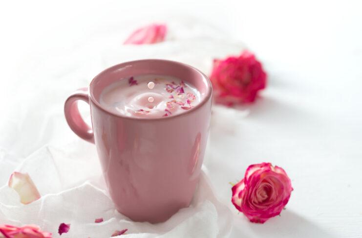 Leche de luna rosa para dormir mejor sobre fondo blanco. Bebida caliente ayurvédica consumida antes de acostarse. Agradable en caso de insomnio, ansiedad e insomnio