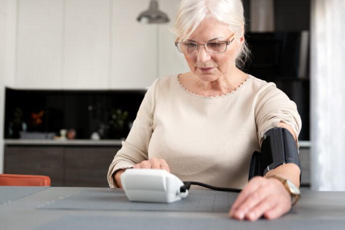 Ältere erwachsene Frau misst Blutdruck zu Hause
