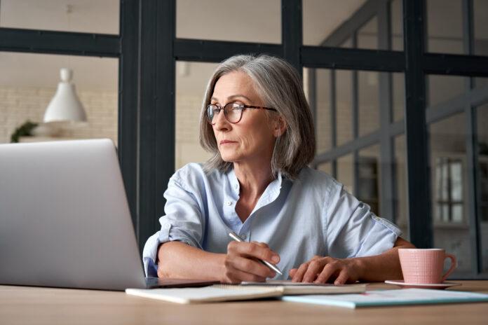 Poważna dojrzała starsza dorosła kobieta oglądająca webinarium szkoleniowe na laptopie pracująca w domu lub w biurze. 60s w średnim wieku bizneswoman robiąca notatki podczas korzystania z technologii komputerowej siedząc przy stole.