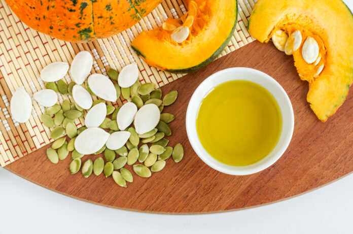 Small white bowl with pumpkin seed oil. Ingredients for healthy eating and preparing homemade face or hair mask. Natural beauty treatment recipe, zero waste concept. Top view, copy space